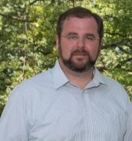 A headshot of Jeffery Holland. He wears a blue shirt and has glasses