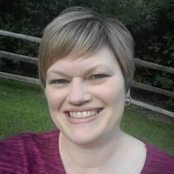 A headshot of Pamela harker. She is smiling and wears a burgundy shirt.